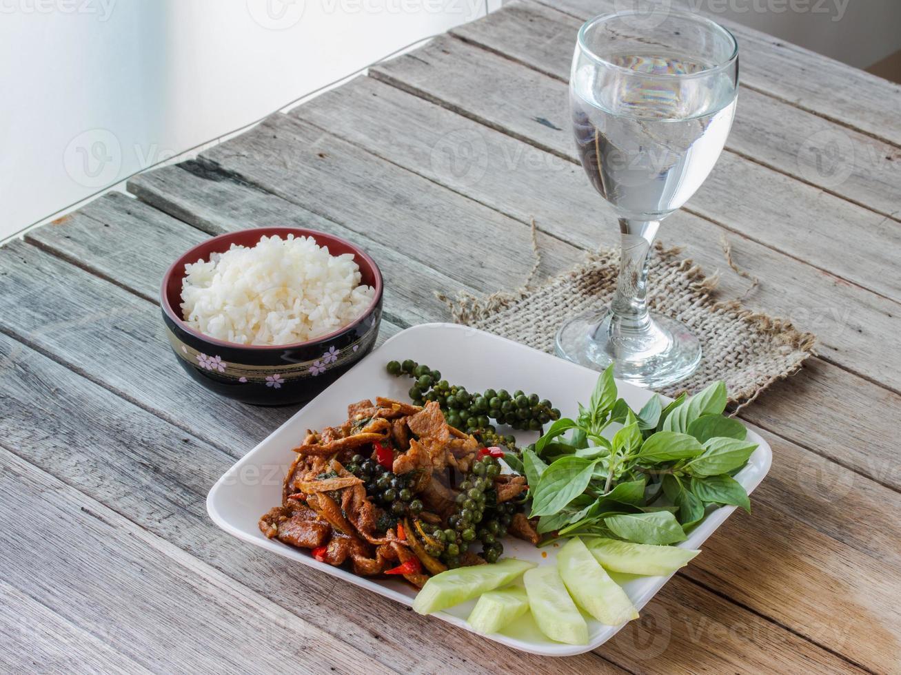 roergebakken met pittig, thais eten, rijst in beker en water foto