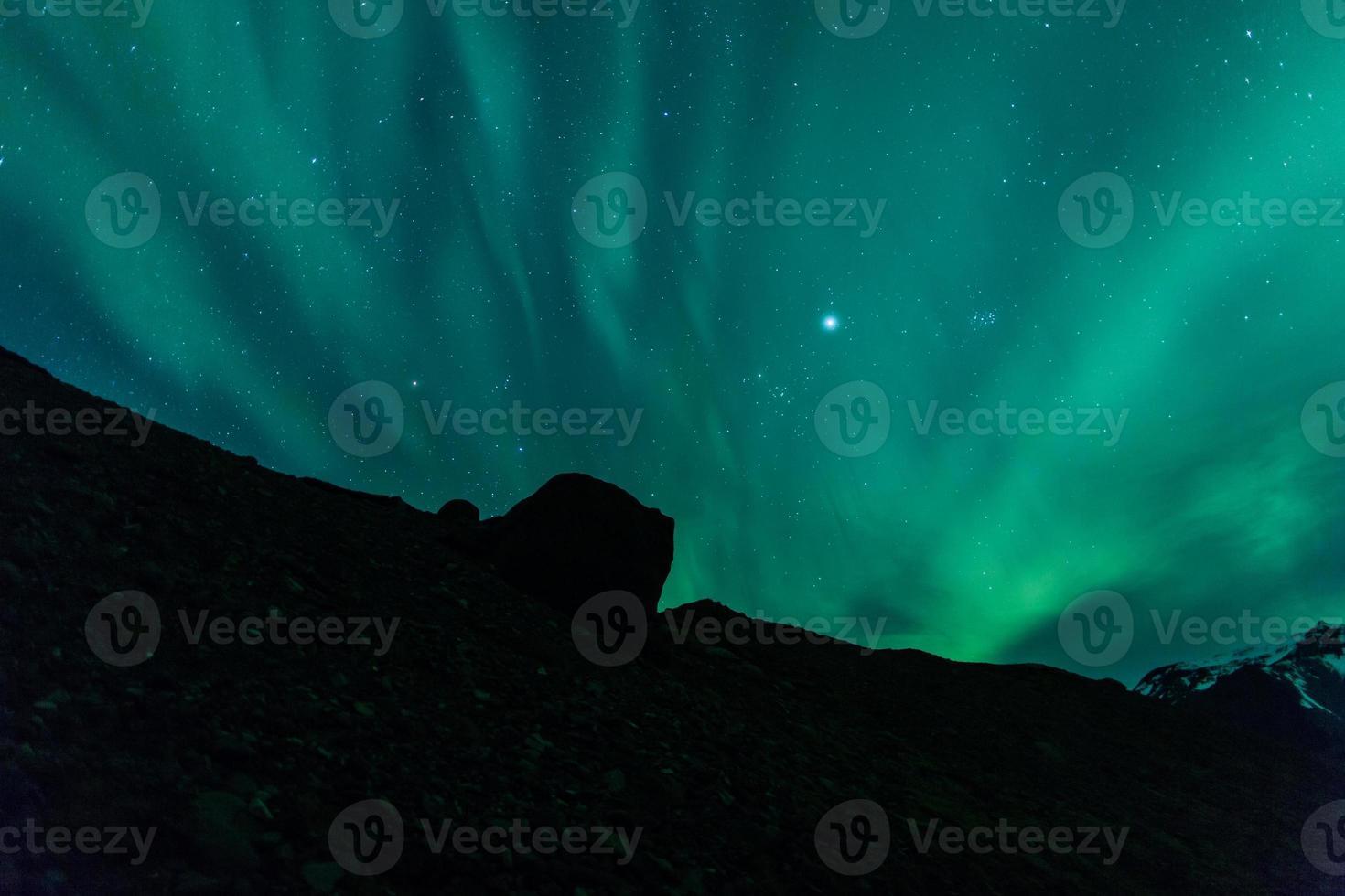 noorderlicht (aurora borealis) achter een rots foto