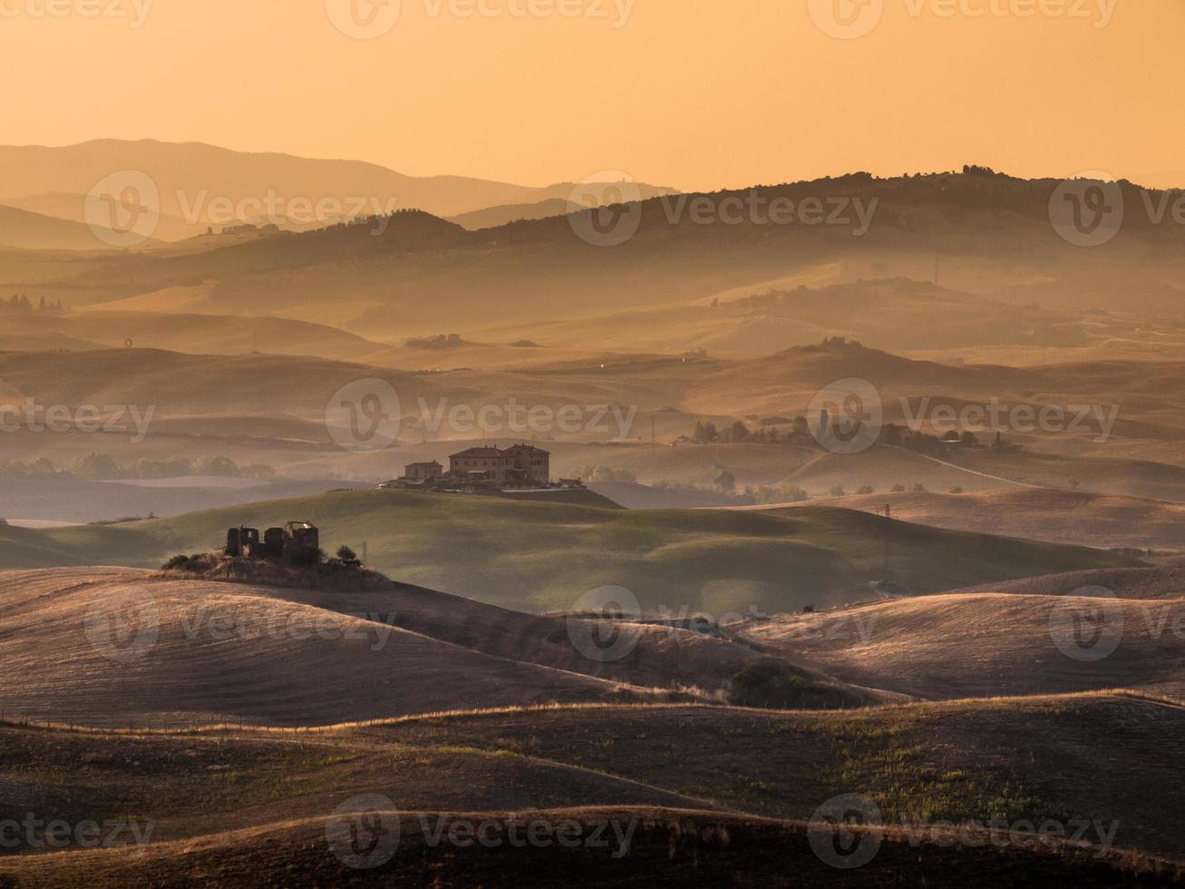 Toscaans platteland met heuvels en boerderijen foto