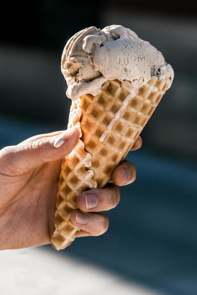 hand met een kegel van chocolade-ijs foto