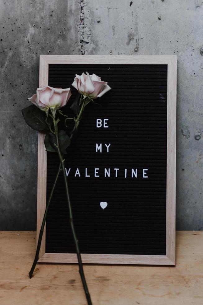 twee roze rozen die tegen een be my valentijnskaart leunen foto