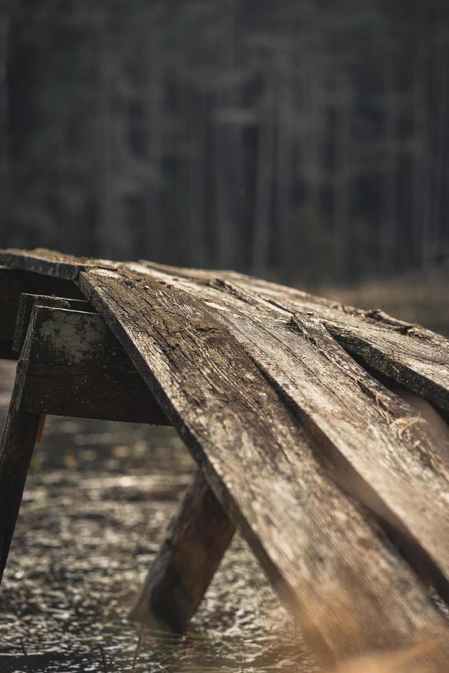 bruine houten loopbrug in het bos foto