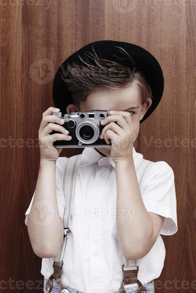 jonge jongen die foto met oude camera neemt