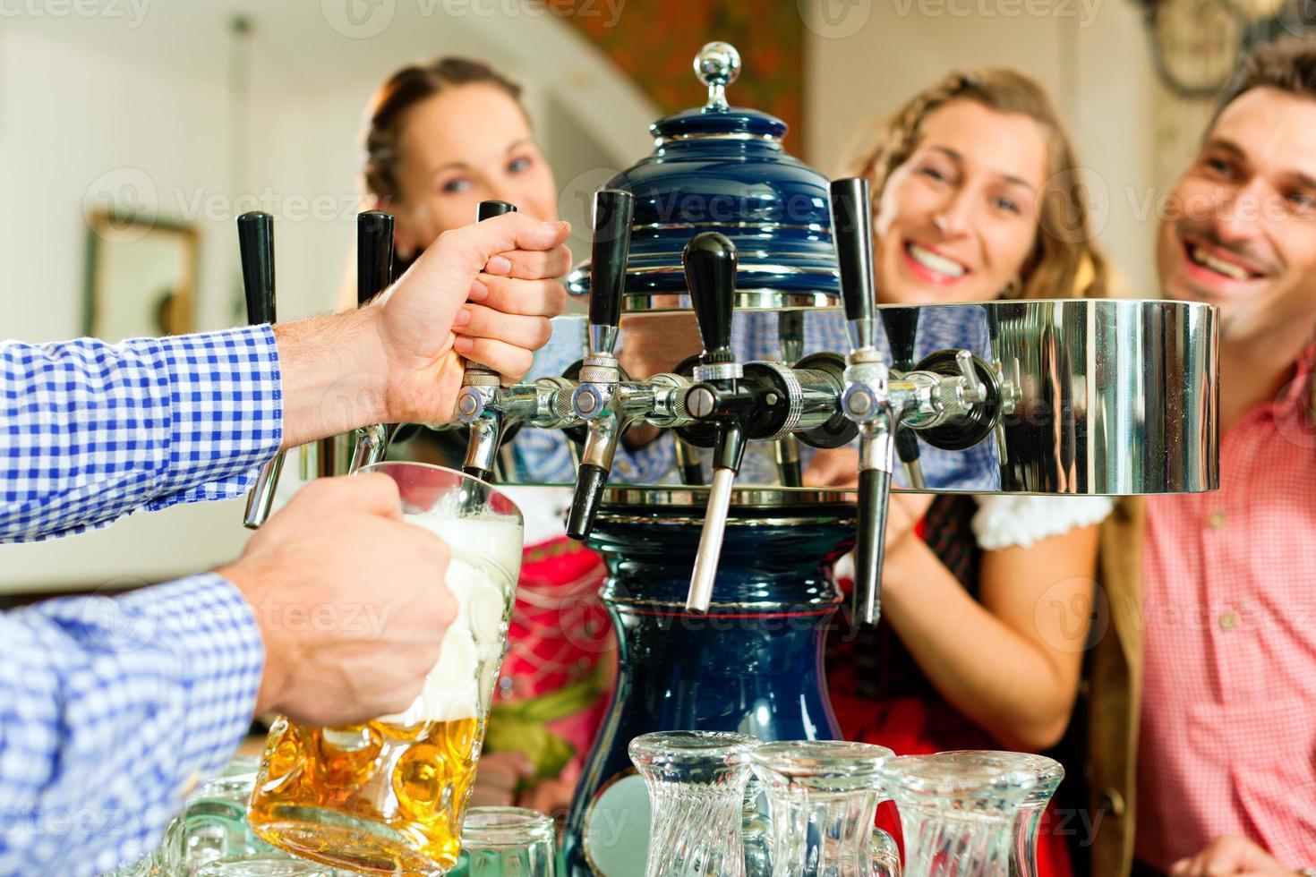 man bier puttend uit de kraan in Beierse pub foto