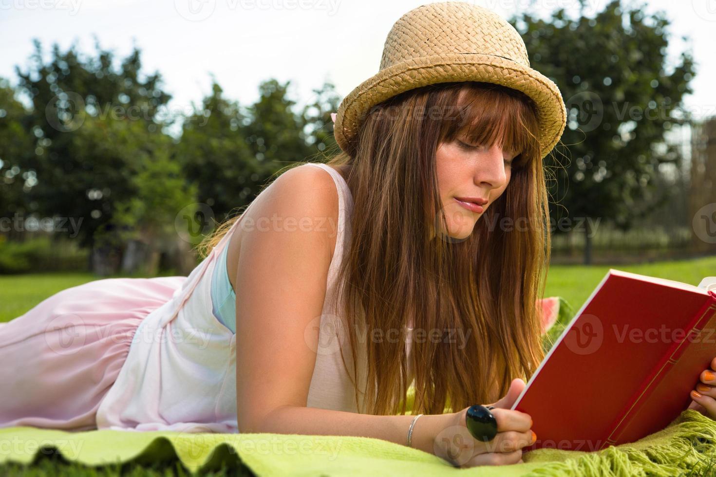aantrekkelijke jonge vrouwelijke leesboek in het park foto