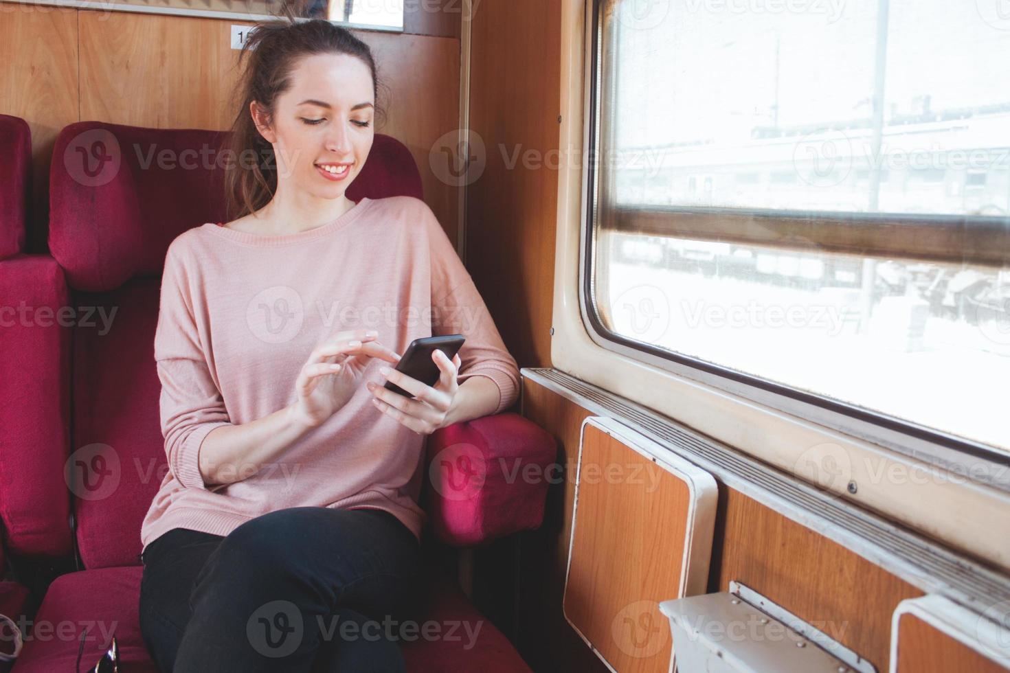 jonge lachende vrouw met behulp van smartphonet reizen op de trein foto
