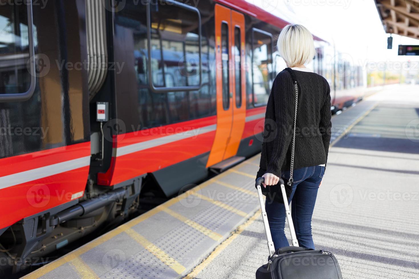 jonge vrouw bij een openluchttreinterminal foto
