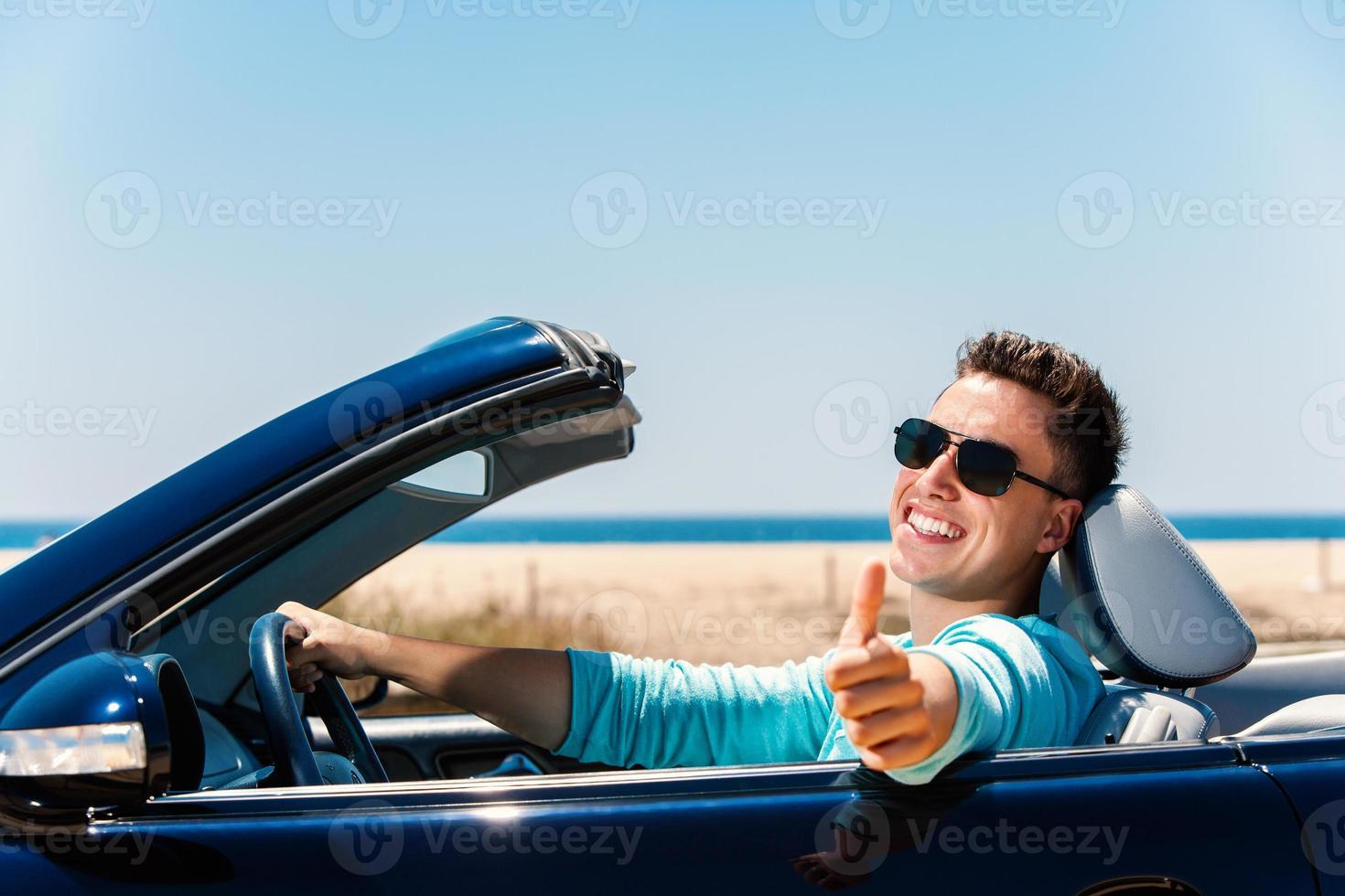 jonge man in cabriolet duimen omhoog doen. foto