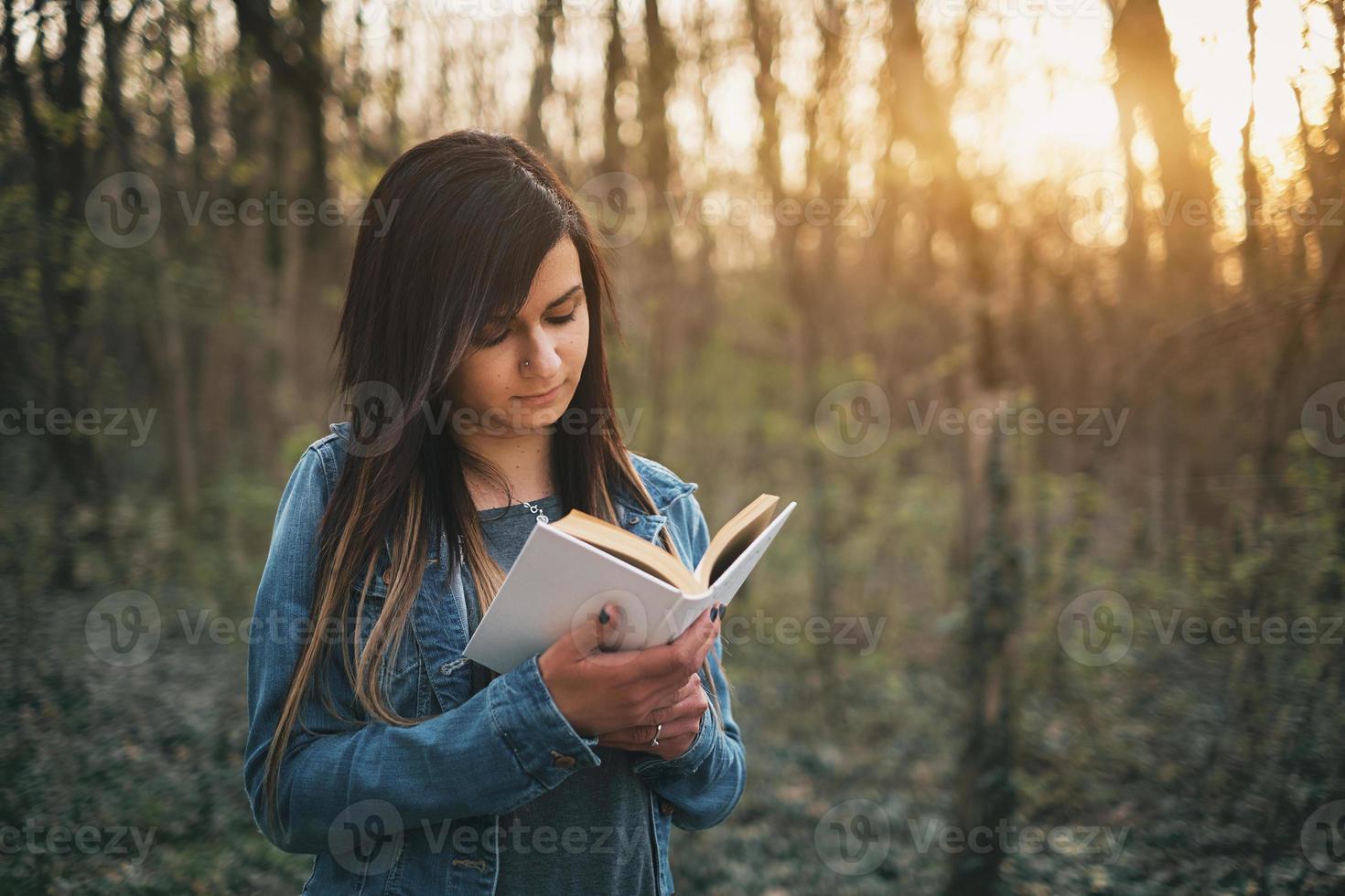 een meisje dat een boek leest in het bos foto