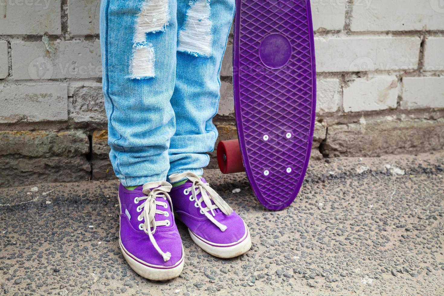 tiener in spijkerbroek staat met skateboard foto