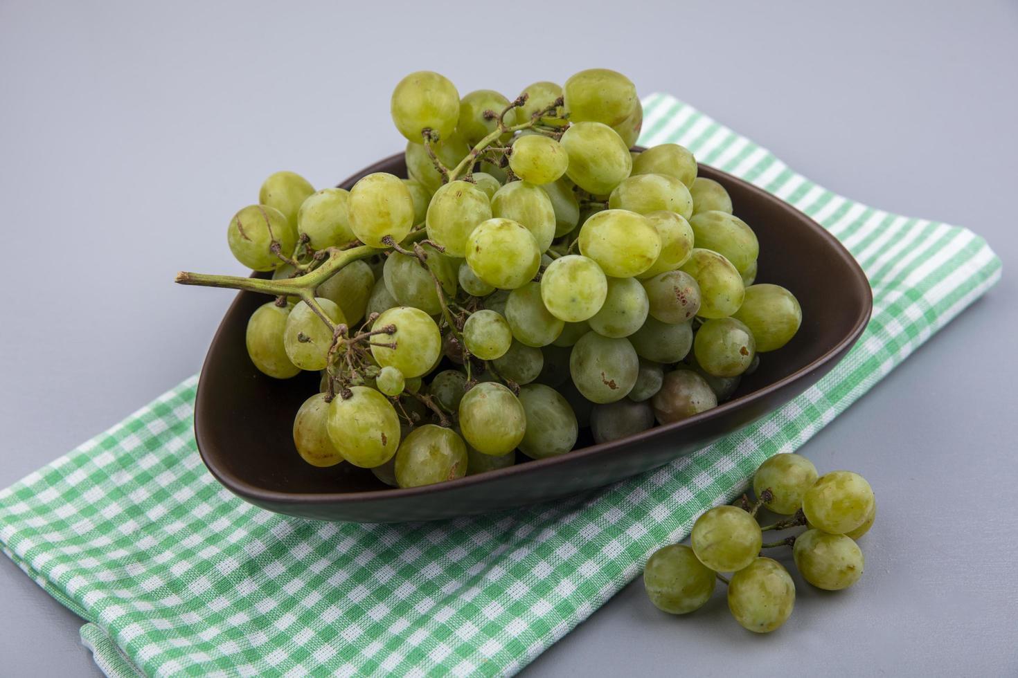 druiven in kom op geruite doek op grijze achtergrond foto