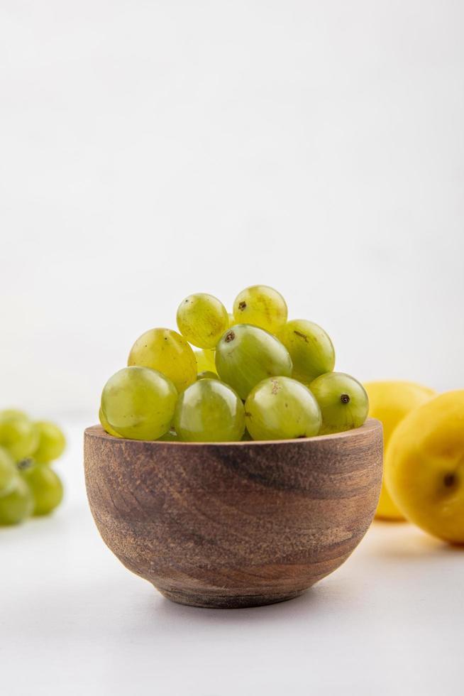 witte druiven in een houten kom op witte achtergrond foto