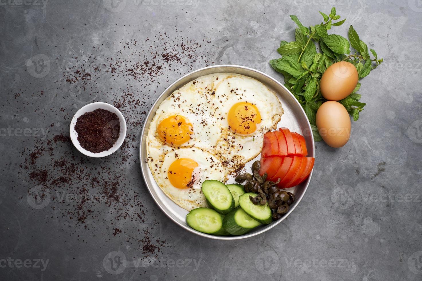 presentatie van gebakken eieren met pepermuntjes, tomaat, olijven, komkommer en sumak foto