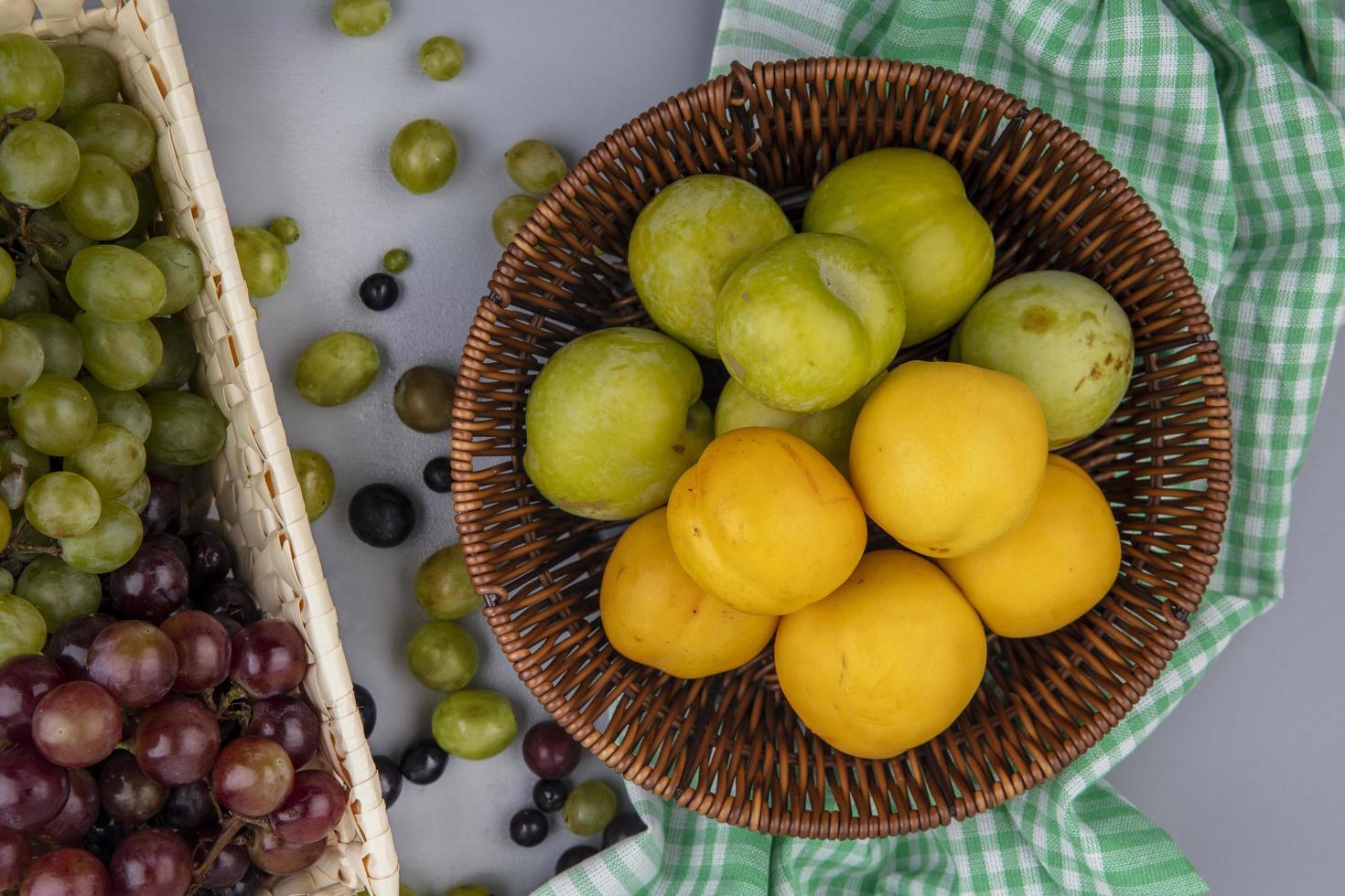 bovenaanzicht van fruit in een mand op geruite doek foto