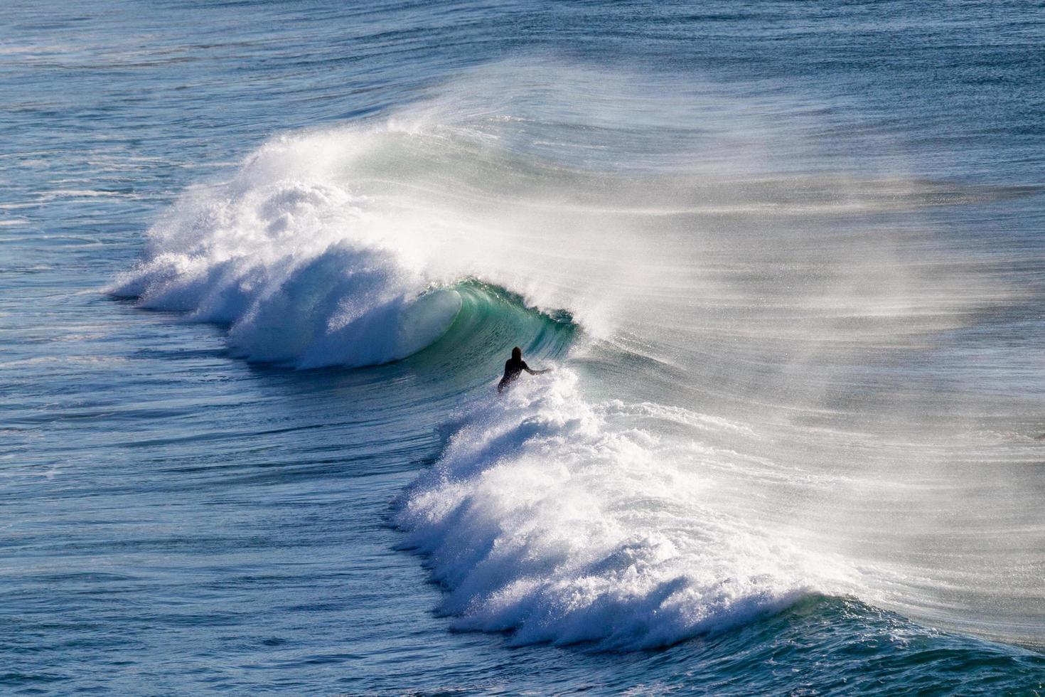 persoon die op een golf surft foto