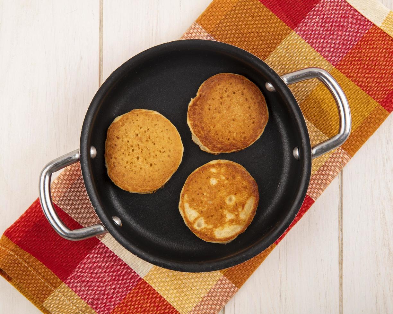 bovenaanzicht van pannenkoeken in pan op geruite doek en houten achtergrond foto