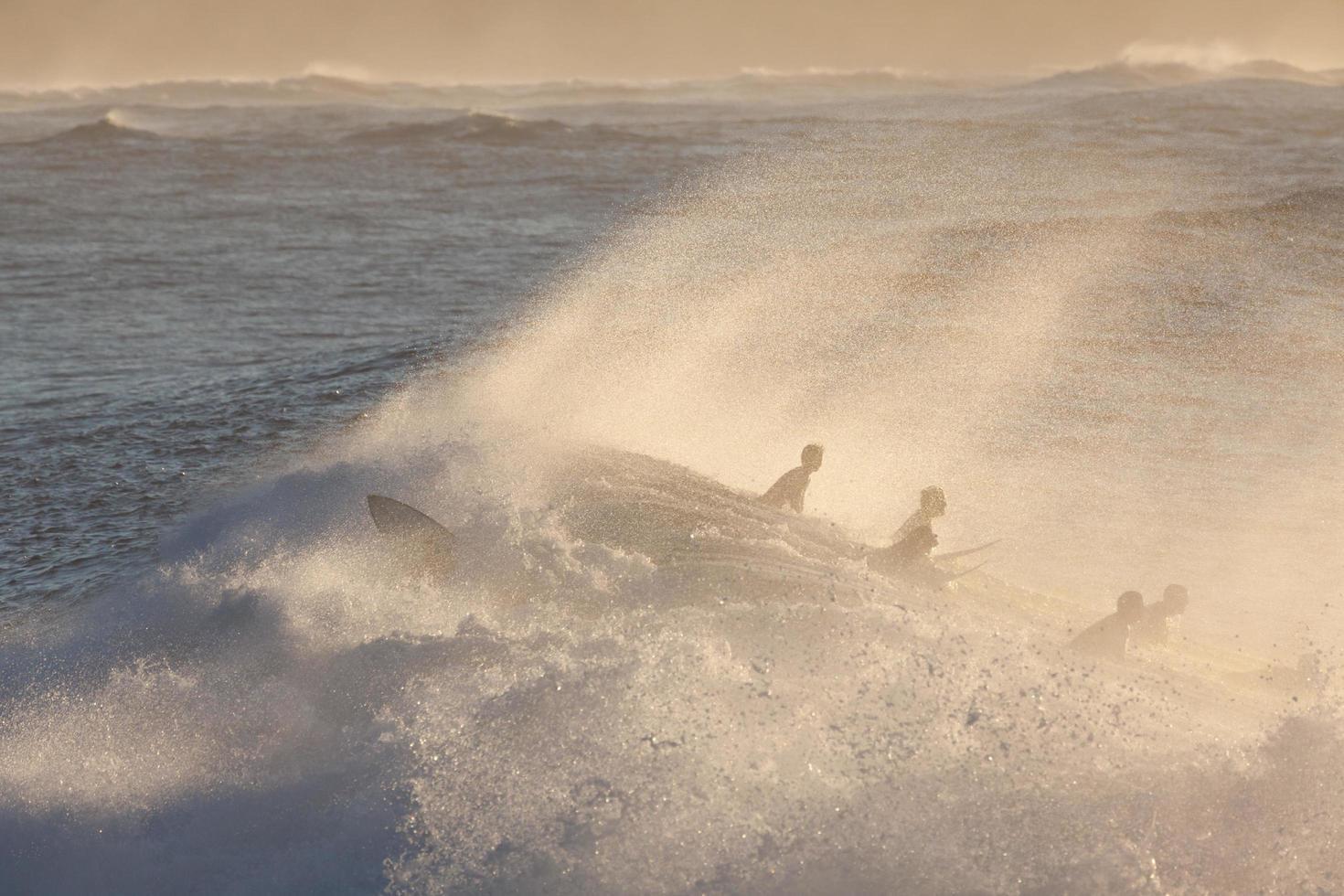 silhouetten van surfers bij zonsondergang foto