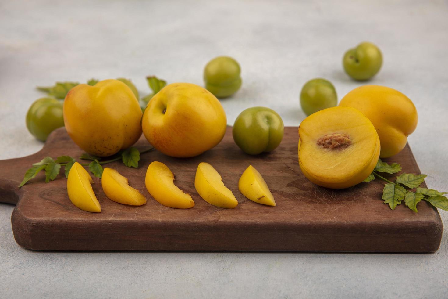 bovenaanzicht van verse gele perziken en pruimen foto