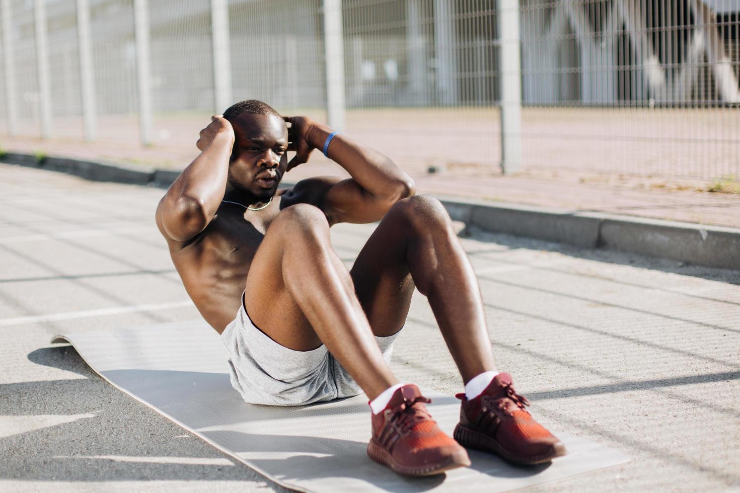 Afro-Amerikaanse man traint zijn buikspieren liggend op de grond buiten foto