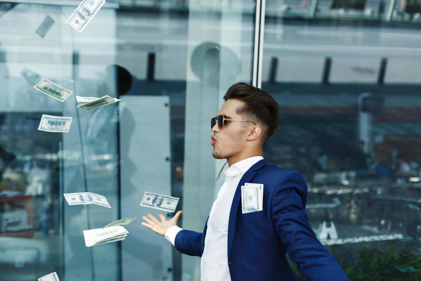 dollars vliegen rond knappe jonge zakenman foto