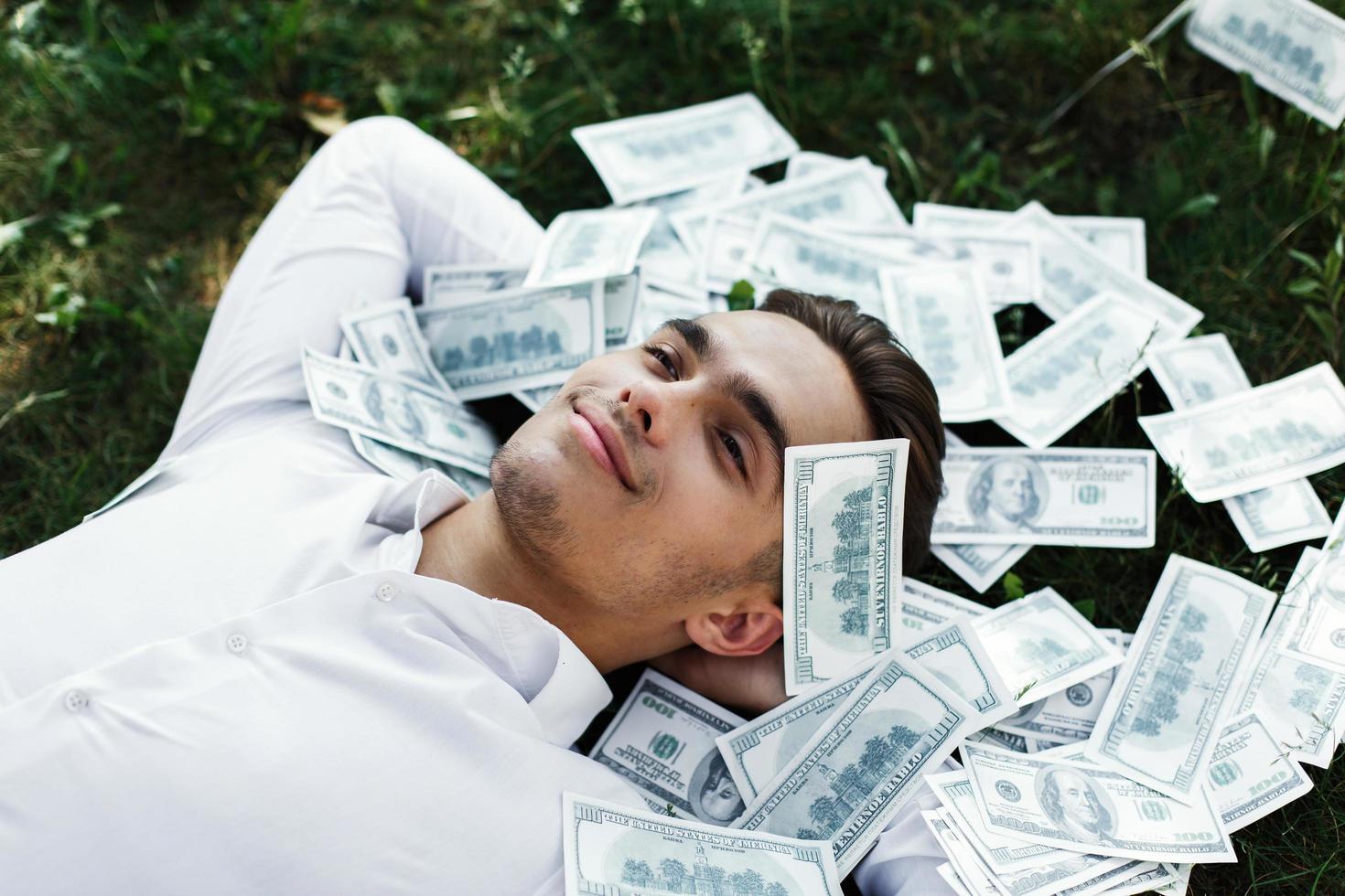 man liggend in het gras met honderd dollarbiljetten foto