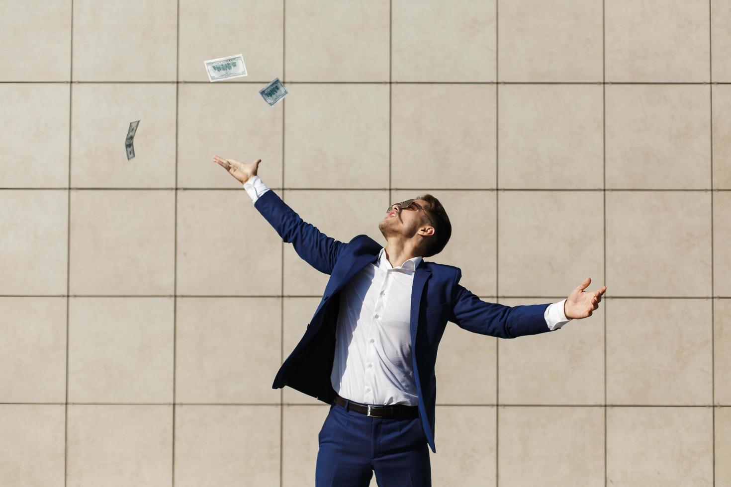 jonge zakenman gooit dollars rond en danst op straat foto