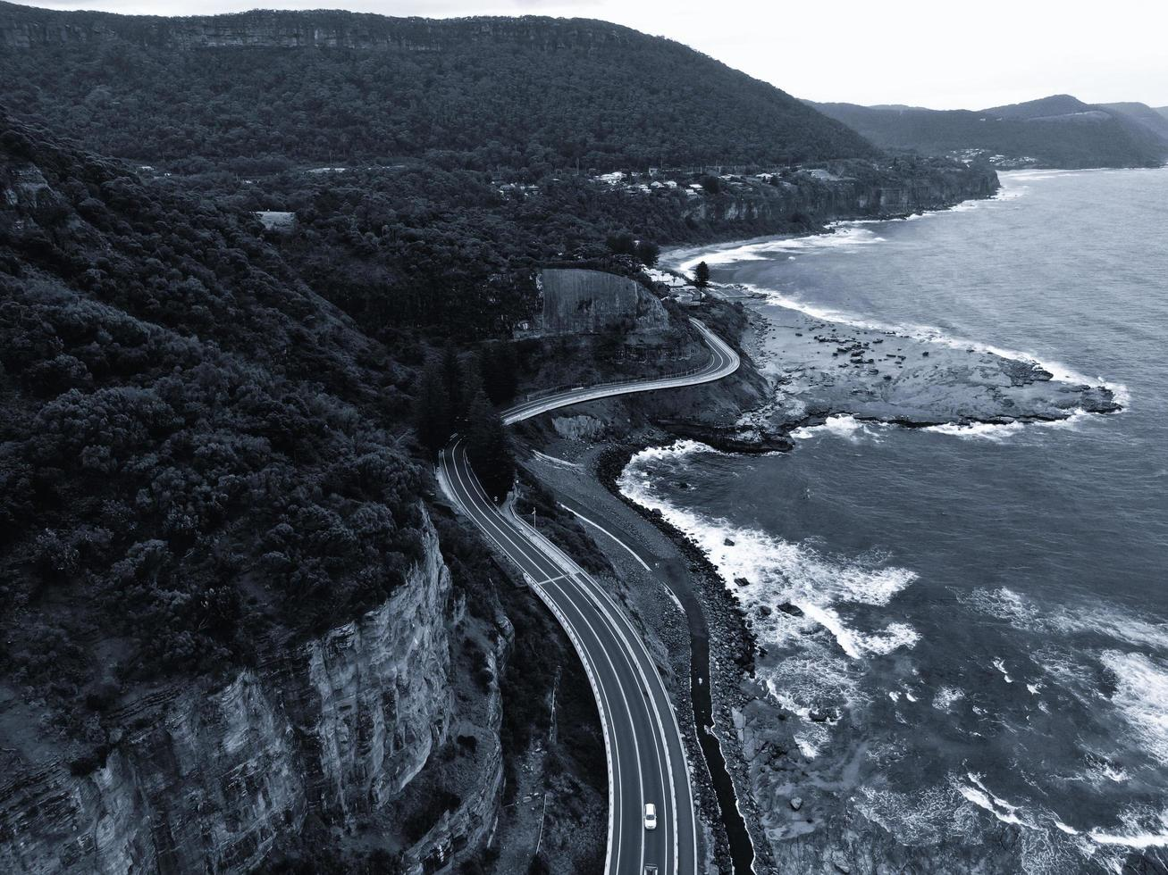 luchtfoto van een weg in de buurt van bergen en de oceaan foto