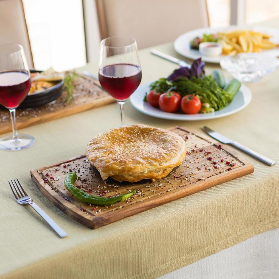 smakelijke vleesmaaltijd met brood met glas rode wijn foto