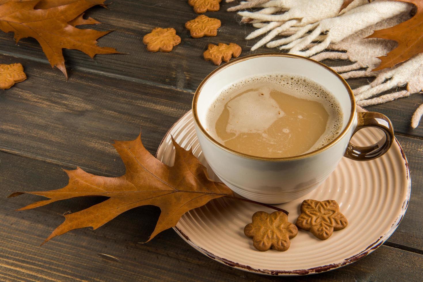 koffiekopje met herfstbladeren en koekjes foto