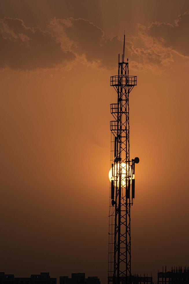 silhouet van een radiotoren met ondergaande zon foto