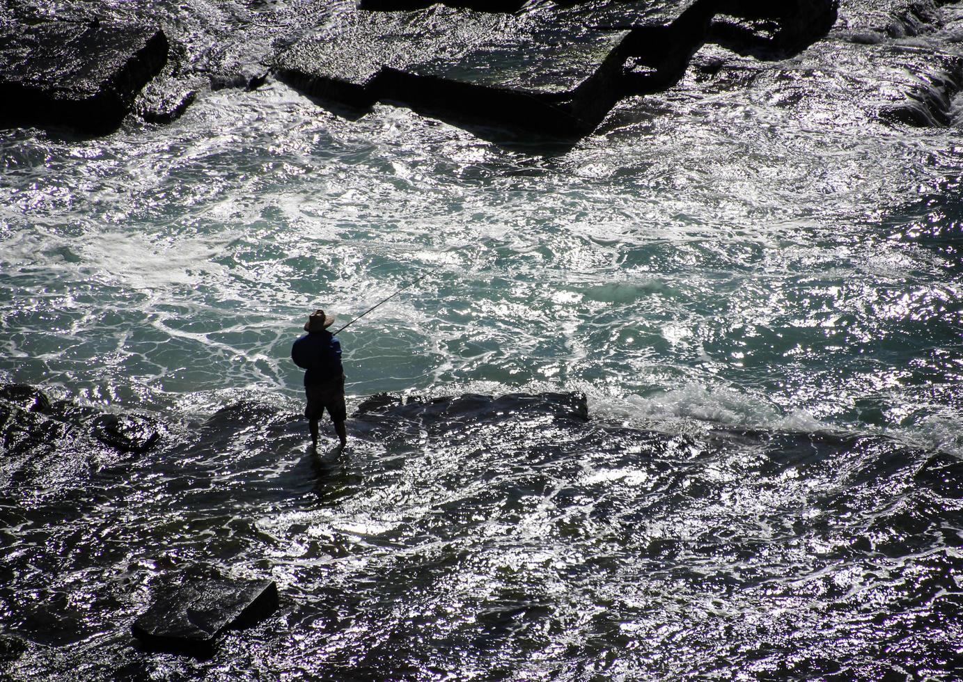 sydney, Australië, 2020 - man aan het vissen terwijl hij in het water waadt foto