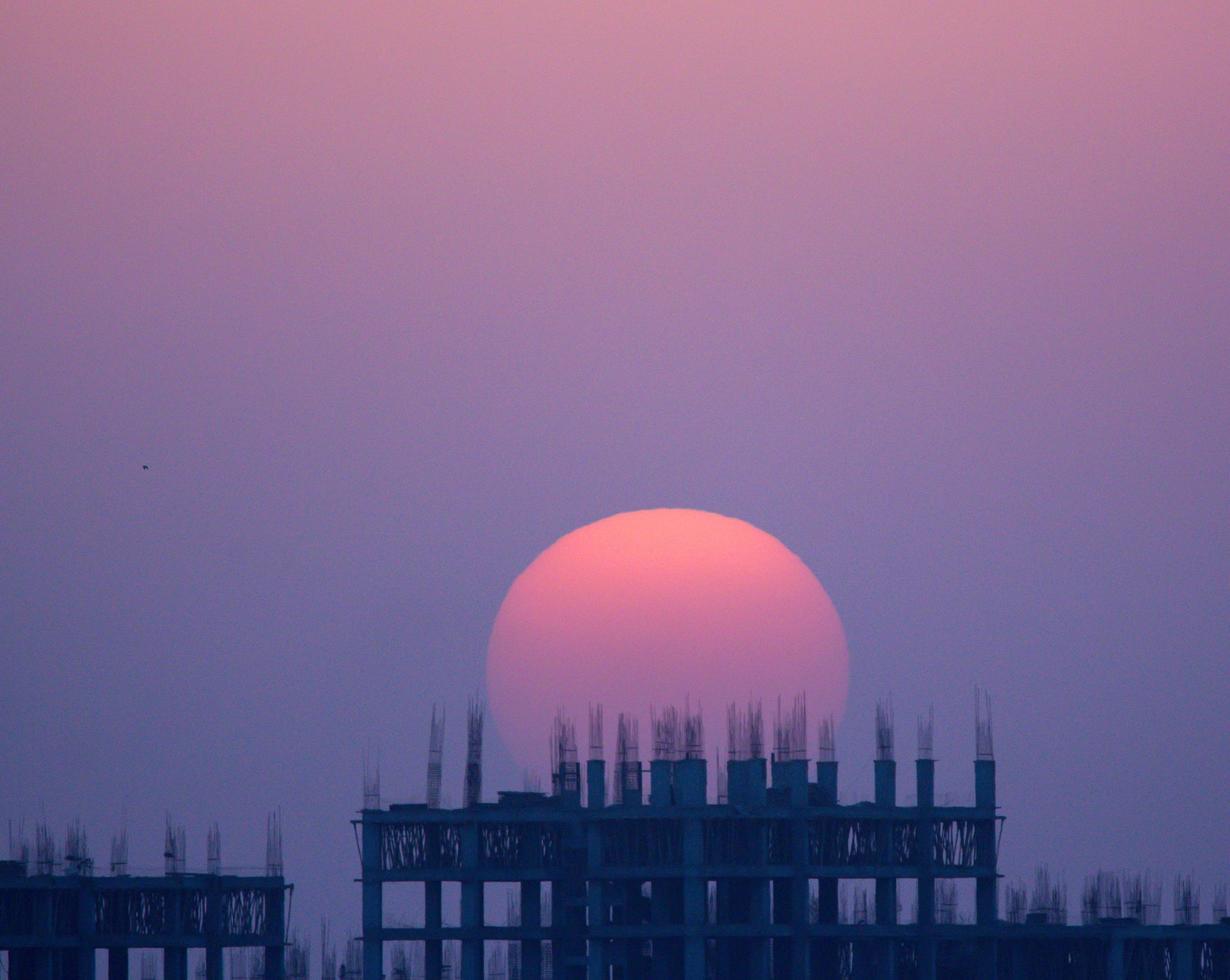 kleurrijke zonsondergang over een gebouw in constructie foto