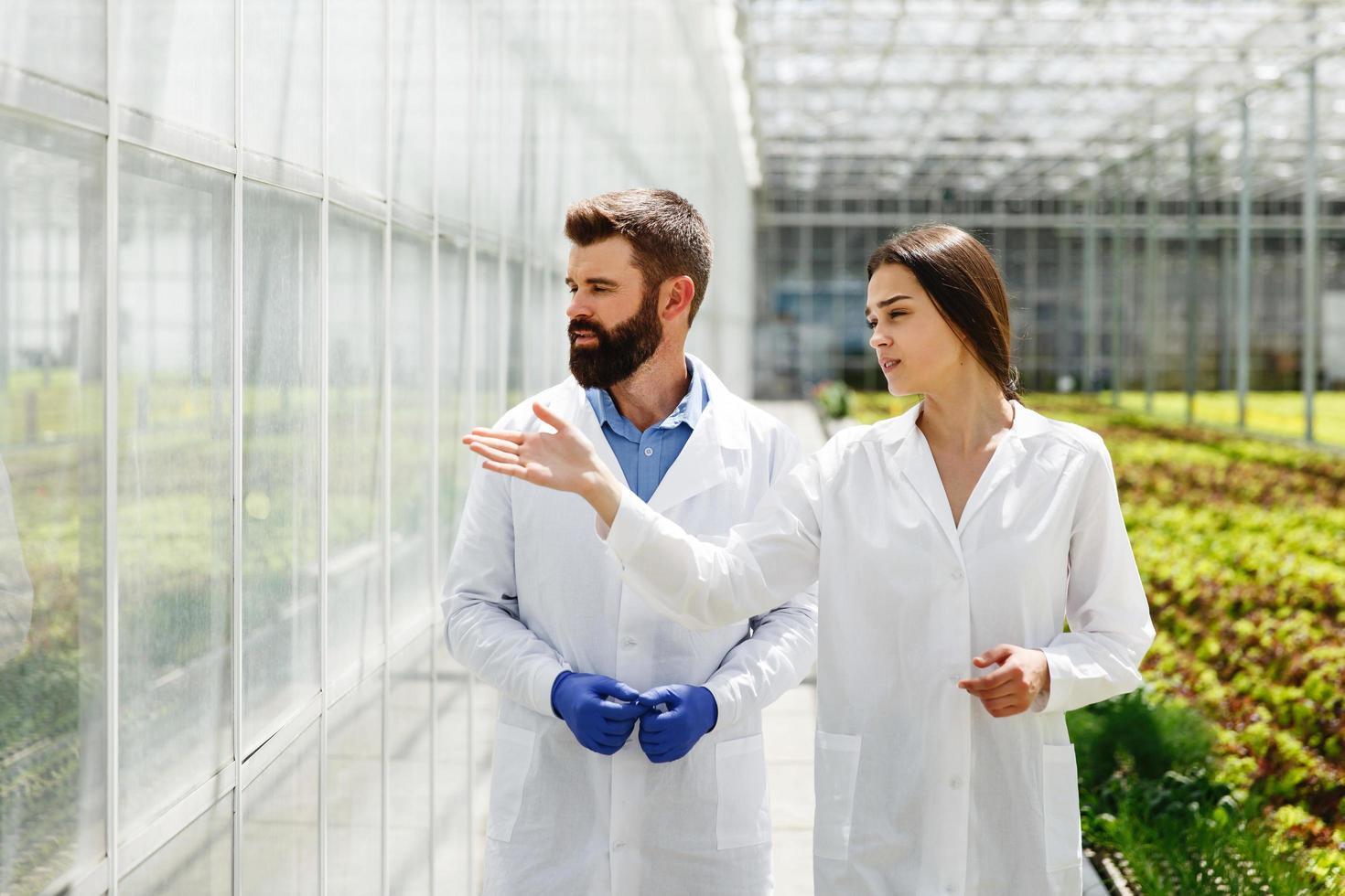 twee onderzoekers in laboratoriumjassen lopen door de kas foto