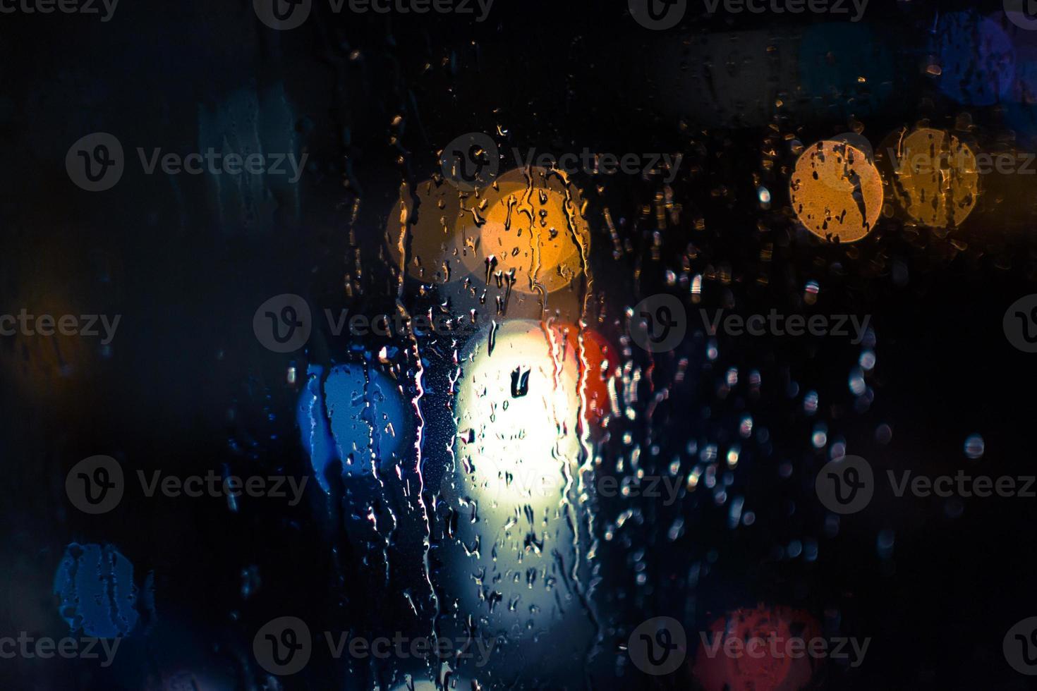autokoplampen en straatverlichting in de regen foto