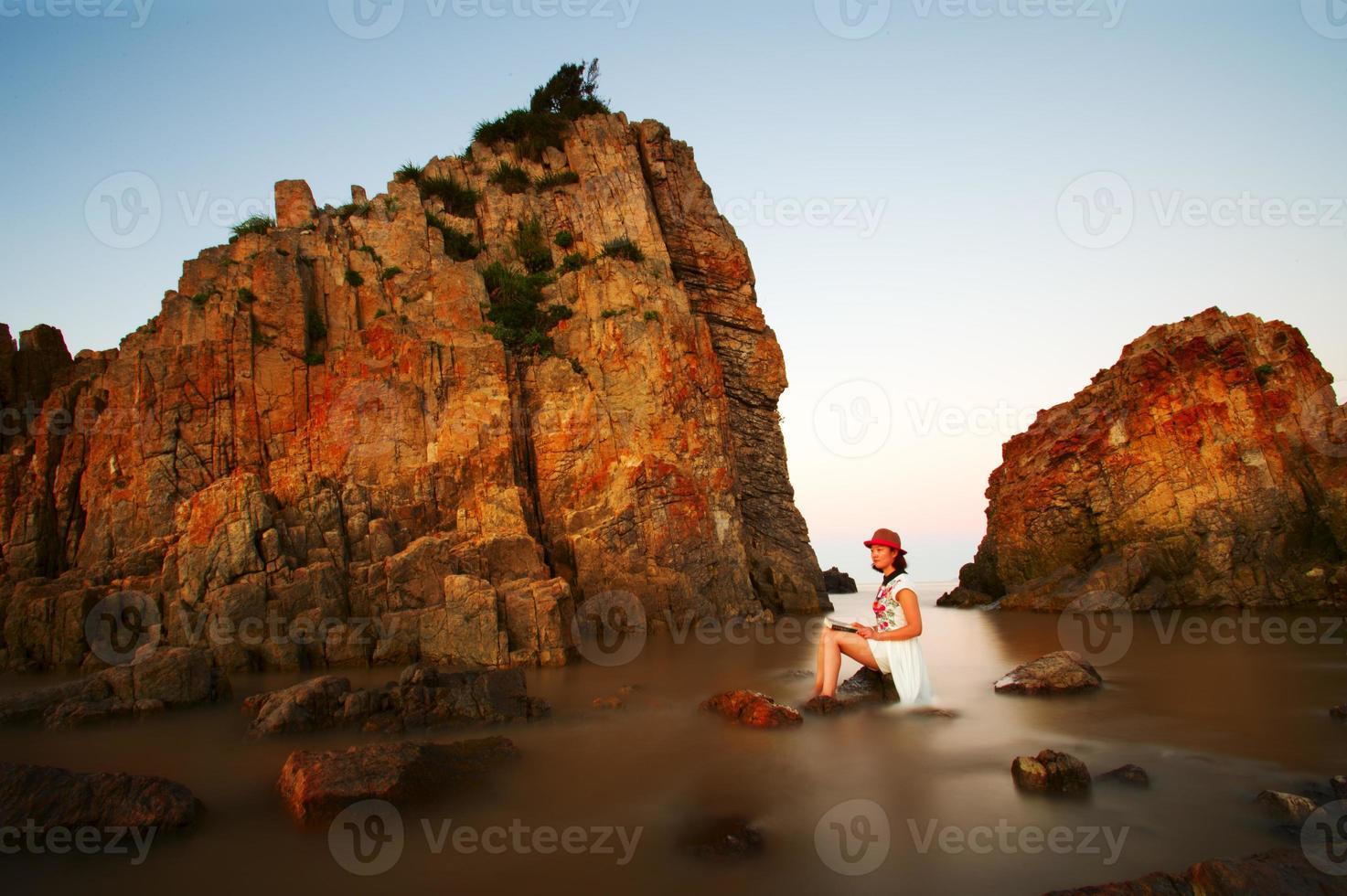 jonge mooie vrouw ontspannen op rotsachtige kust? foto