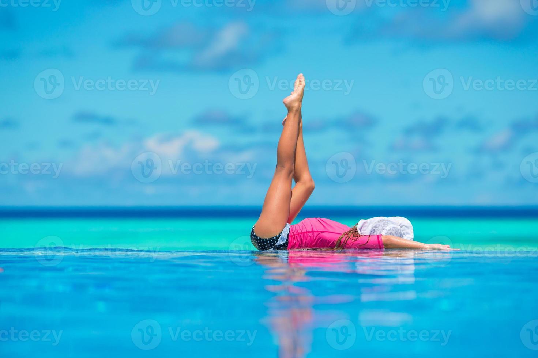gelukkig mooi meisje met plezier in het buitenzwembad foto