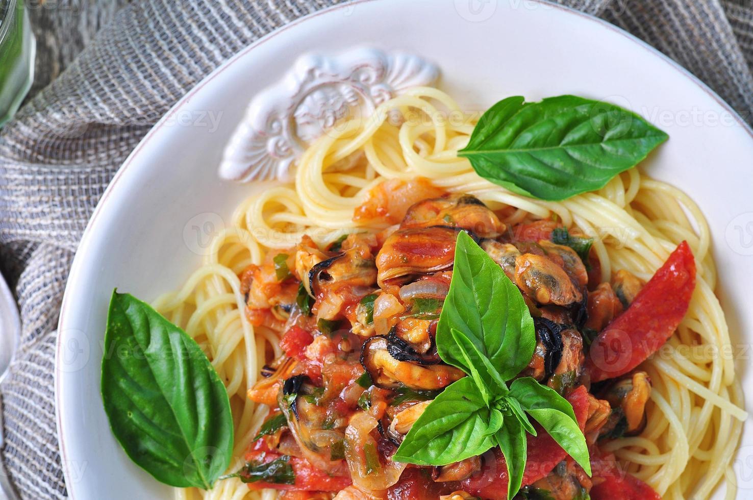 pasta met mosselen, pepperoni, spek, tomaat en basilicum foto