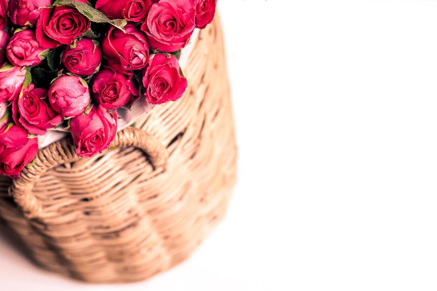 mooi boeket van rode rozen in mand, geïsoleerd op wit foto
