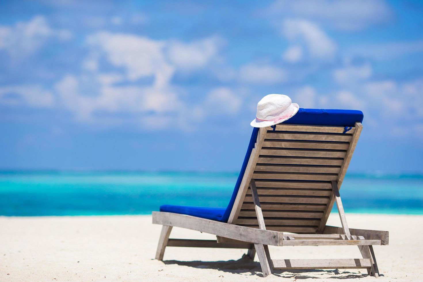 lounge stoel en witte hoed op een tropisch strand foto