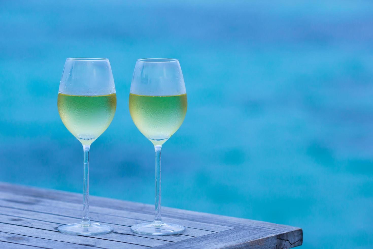 witte wijnglazen bij een pool foto