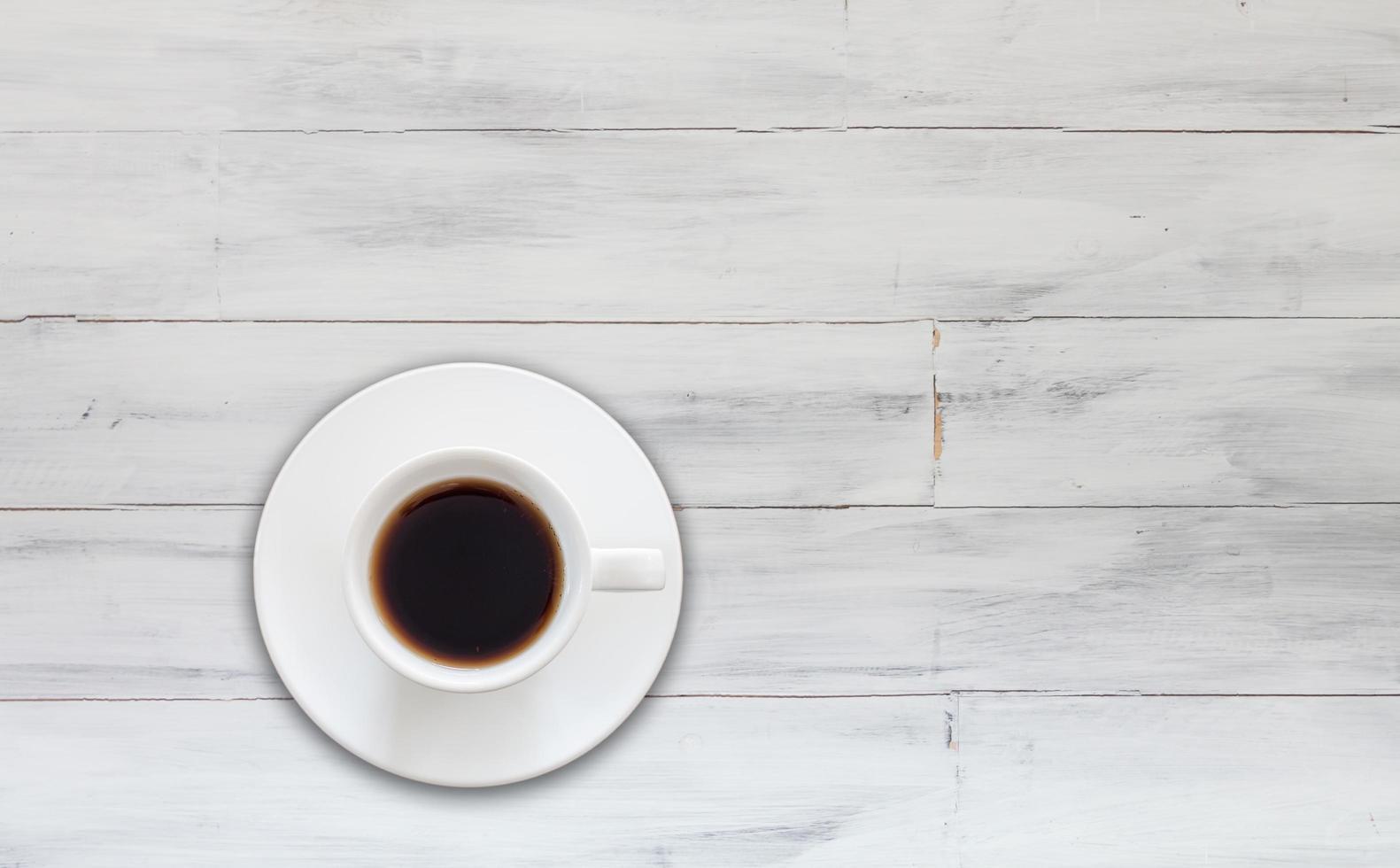 bovenaanzicht van koffiekopje op witte houten achtergrond foto