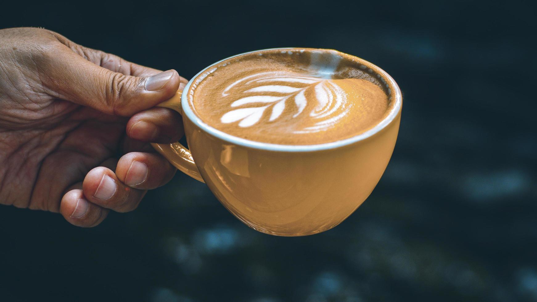 hand met een latte in een gele mok foto