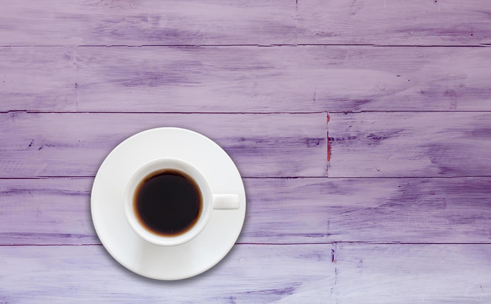 bovenaanzicht van koffiekopje op een paarse houten achtergrond foto