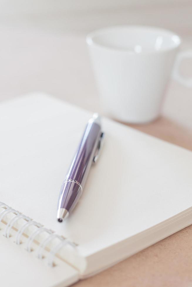 pen op een notitieboekje met een koffiekopje foto