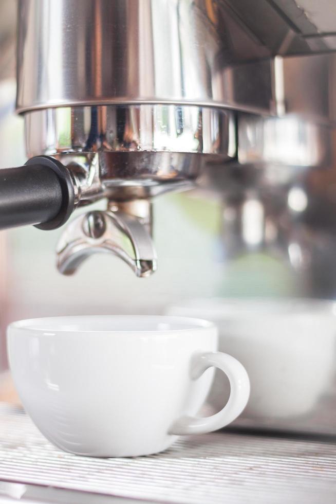 wit espressokopje onder een espresso-infuus foto