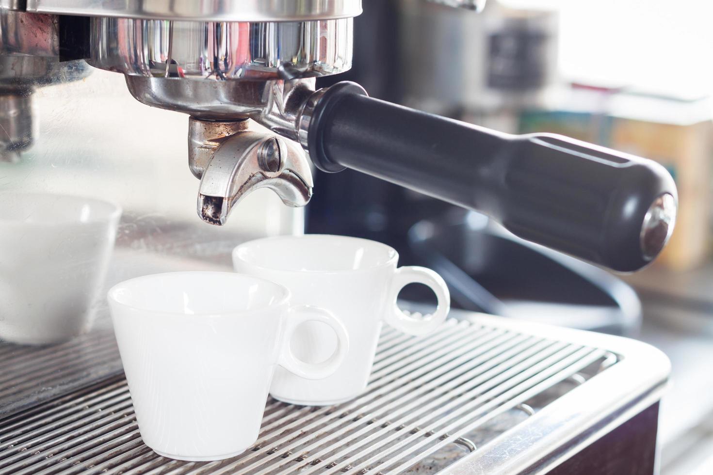 espressokopjes onder een espresso-infuus foto