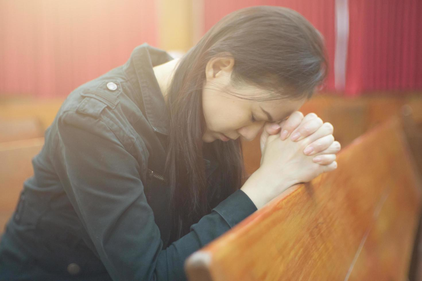 mooie Aziatische vrouw die in de ochtend bidt in de kerk foto