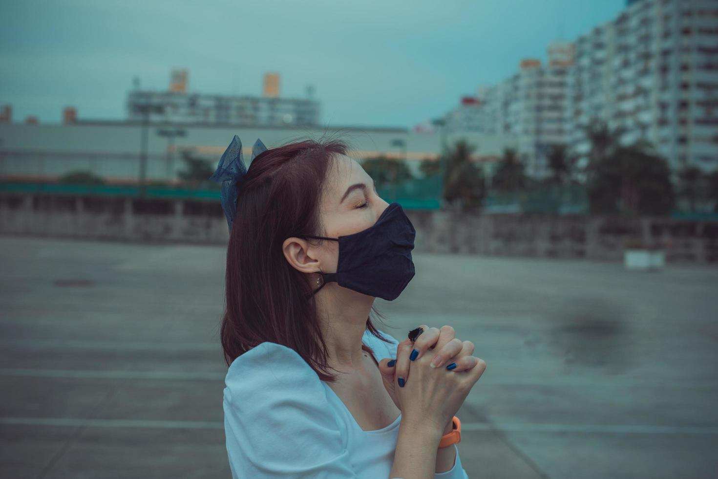 mooie vrouw met handen bidden tot god voor mensen in de stad foto