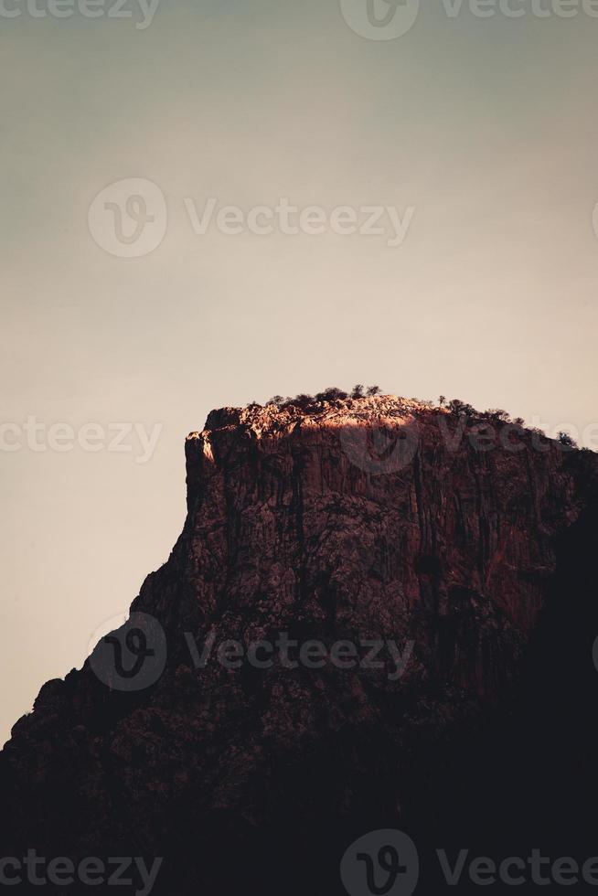 gigantische rotsachtige top in de bergen, rood gekleurd door de zonsondergang foto