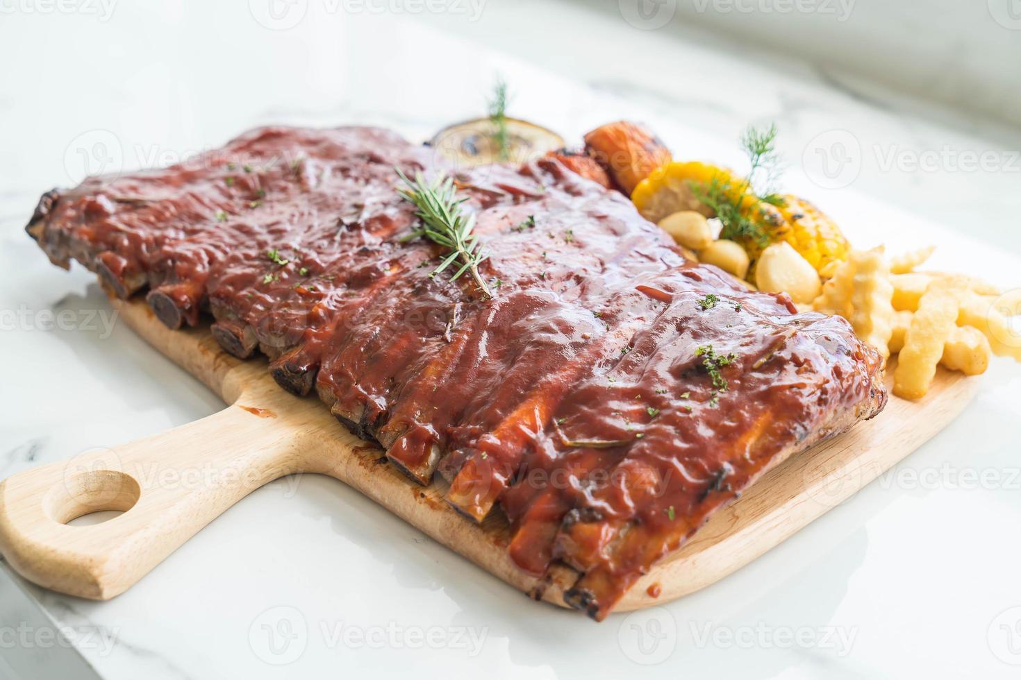 gegrilde bbq-ribben met groenten en frietjes op houten snijplank foto